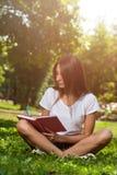 Estudiante moreno Girl Sitting en hierba verde en parque imagenes de archivo