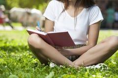 Estudiante moreno Girl Sitting en hierba verde en parque fotos de archivo libres de regalías