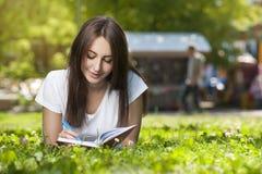 Estudiante moreno Girl Sitting en hierba verde en parque foto de archivo libre de regalías
