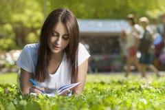 Estudiante moreno Girl Sitting en hierba verde en parque imagen de archivo