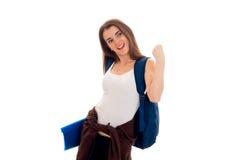 Estudiante moreno joven atractivo con la mochila azul en su presentación de los hombros aislada en el fondo blanco Imagen de archivo libre de regalías