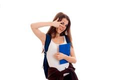 Estudiante moreno joven de Cutie con la mochila azul en su presentación de los hombros aislada en el fondo blanco Foto de archivo libre de regalías