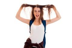 Estudiante moreno joven divertido con la mochila azul en su presentación de los hombros aislada en el fondo blanco Fotos de archivo