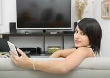 Estudiante moreno joven que se sienta en el sofá con el teléfono Fotografía de archivo