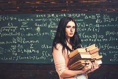 Estudiante moreno que camina con dos montones de libros delante del tablero verde por completo de escritura Preparaci?n del estud foto de archivo libre de regalías