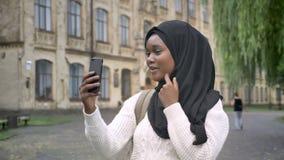 Estudiante musulmán africano joven en el hijab que tiene charla video a través del teléfono, colocándose en parque cerca de la un almacen de metraje de vídeo