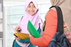 Estudiante musulmán del niño que discute algo en biblioteca Imágenes de archivo libres de regalías