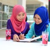 Estudiante musulmán joven hermoso que comparte la información junta Imagen de archivo libre de regalías
