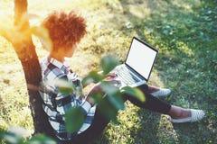 Estudiante negro rizado del feemale con el ordenador portátil en parque Fotos de archivo libres de regalías