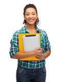 Estudiante negro sonriente con las carpetas y PC de la tableta Fotos de archivo