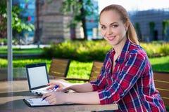 Estudiante o colegiala adolescente hermoso que hace la preparación en parque Imagenes de archivo