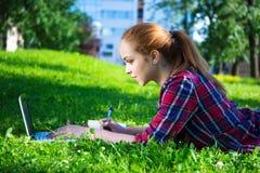 Estudiante o colegiala adolescente que miente en parque con el ordenador portátil Imágenes de archivo libres de regalías