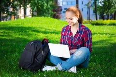 Estudiante o colegiala adolescente que se sienta con el ordenador portátil en parque Imágenes de archivo libres de regalías