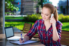 Estudiante o colegiala feliz que habla en el teléfono móvil en parque Fotografía de archivo libre de regalías
