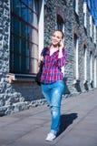 Estudiante o colegiala que camina y que habla en el teléfono móvil Imagen de archivo libre de regalías