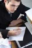 Estudiante o escritura del hombre de negocios algo en el papel en blanco sh Fotos de archivo libres de regalías