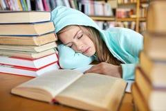 Estudiante o mujer con los libros que duerme en biblioteca Imagen de archivo