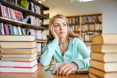 Estudiante o mujer joven aburrido con los libros en biblioteca Imágenes de archivo libres de regalías