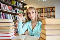 Estudiante o mujer joven aburrido con los libros en biblioteca Imagen de archivo libre de regalías