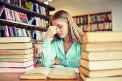 Estudiante o mujer joven aburrido con los libros en biblioteca Fotos de archivo