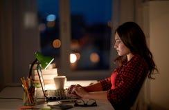 Estudiante o mujer que mecanografía en el ordenador portátil en el hogar de la noche Imágenes de archivo libres de regalías