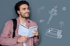 Estudiante optimista que lee un libro y que piensa en otros planetas Imágenes de archivo libres de regalías