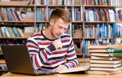 Estudiante pensativo con el ordenador portátil que estudia en la biblioteca de universidad Fotos de archivo libres de regalías