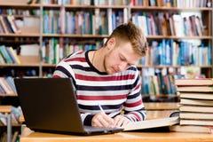 Estudiante pensativo con el ordenador portátil que estudia en la biblioteca de universidad Foto de archivo libre de regalías