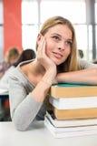 Estudiante pensativo con los libros en sala de clase Fotografía de archivo libre de regalías