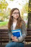 Estudiante pensativo con los vidrios que se sientan en banco Fotografía de archivo libre de regalías