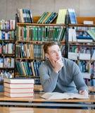 Estudiante pensativo en una biblioteca que mira para arriba Imagenes de archivo