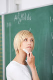 Estudiante pensativo With Hand On Chin Solving Sums On Chalkboard Imagenes de archivo