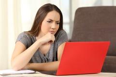 Estudiante pensativo que estudia en línea con un ordenador portátil Imagenes de archivo
