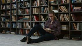 Estudiante pensativo que lee un libro en biblioteca del campus almacen de video