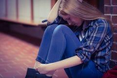 Estudiante pensativo que se sienta en el piso contra la pared Imagen de archivo libre de regalías