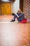 Estudiante pensativo que se sienta en el piso contra la pared Fotografía de archivo libre de regalías