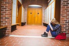 Estudiante pensativo que se sienta en el piso contra la pared Imagenes de archivo