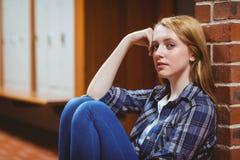 Estudiante pensativo que se sienta en el piso contra la pared y que mira la cámara Imagenes de archivo