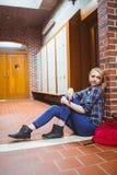 Estudiante pensativo que se sienta en el piso contra la pared y que mira la cámara Imagen de archivo