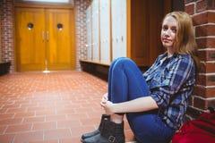 Estudiante pensativo que se sienta en el piso contra la pared y que mira la cámara Fotos de archivo libres de regalías