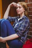Estudiante pensativo que se sienta en el piso contra la pared y que mira la cámara Fotos de archivo