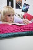 Estudiante pensativo Writing In Book en cama Imagen de archivo