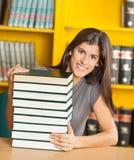 Estudiante With Piled Books que asiste en la tabla Foto de archivo
