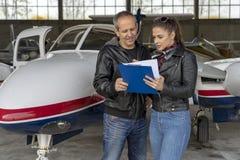 Estudiante Pilot e instructor Going Through un piloto prevuelo Checklist imagen de archivo libre de regalías
