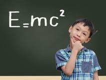 Estudiante por la pizarra con e=mc2 Imagen de archivo libre de regalías