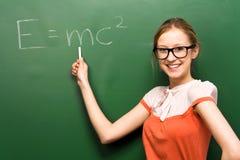 Estudiante por la pizarra con e=mc2 Fotografía de archivo