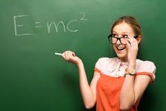 Estudiante por la pizarra con e=mc2 Fotos de archivo
