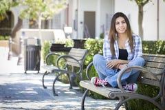 Estudiante Portrait de la raza mixta en banco del campus de la escuela Imagen de archivo