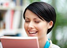 Estudiante positivo con el libro en la biblioteca Foto de archivo