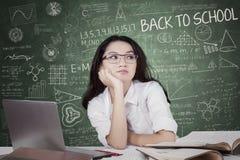 Estudiante precioso pensativo en sala de clase Foto de archivo libre de regalías